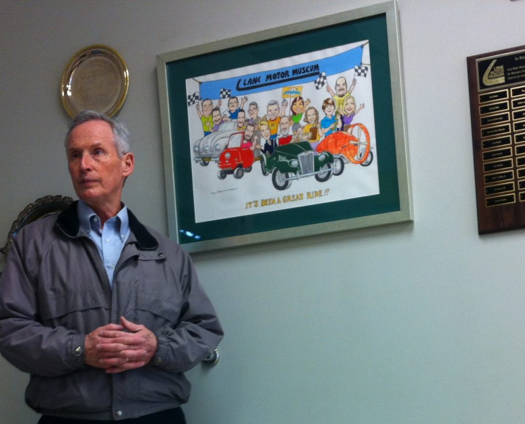 Artist with cartoons of cars at Lane Motor Museum